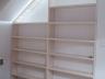 Drewniany podświetlany regał na książki ozdobiony panelem ażurowym